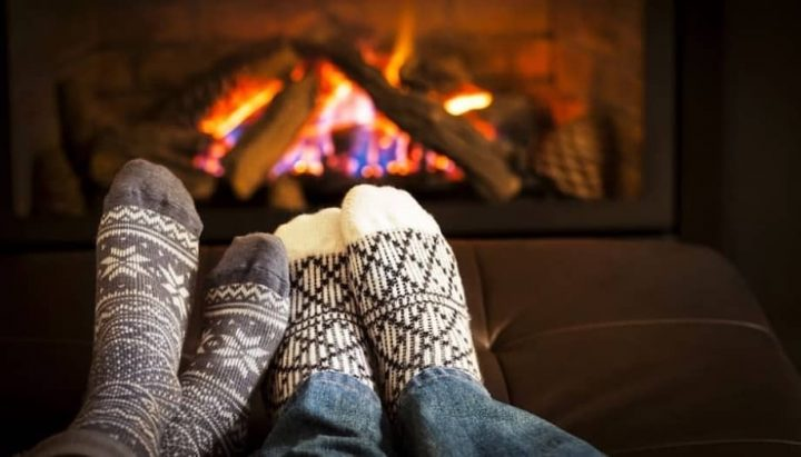 Two pairs of feet Argyll socks roaring fire