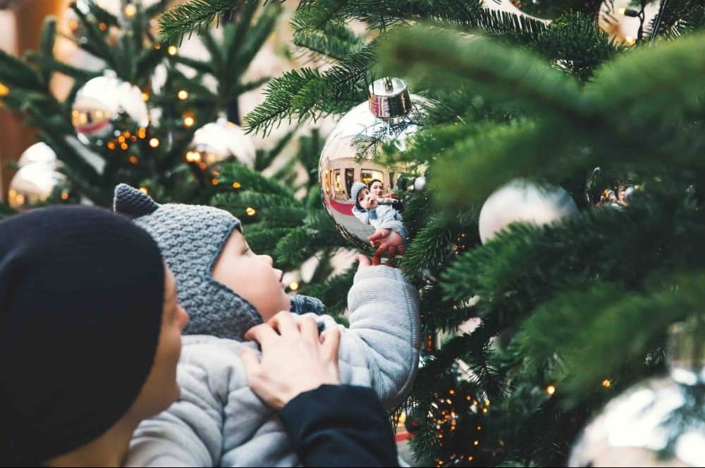Woman in blue hat hold baby christmas tree giant silver baubles