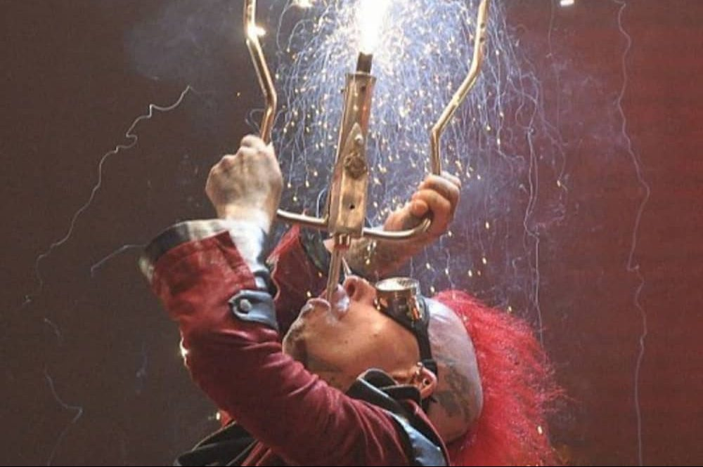 Circus of Horrors Psycho Asylum tour sword swallower red hair goggles and burgundy frock coat sword in throat with firework attached