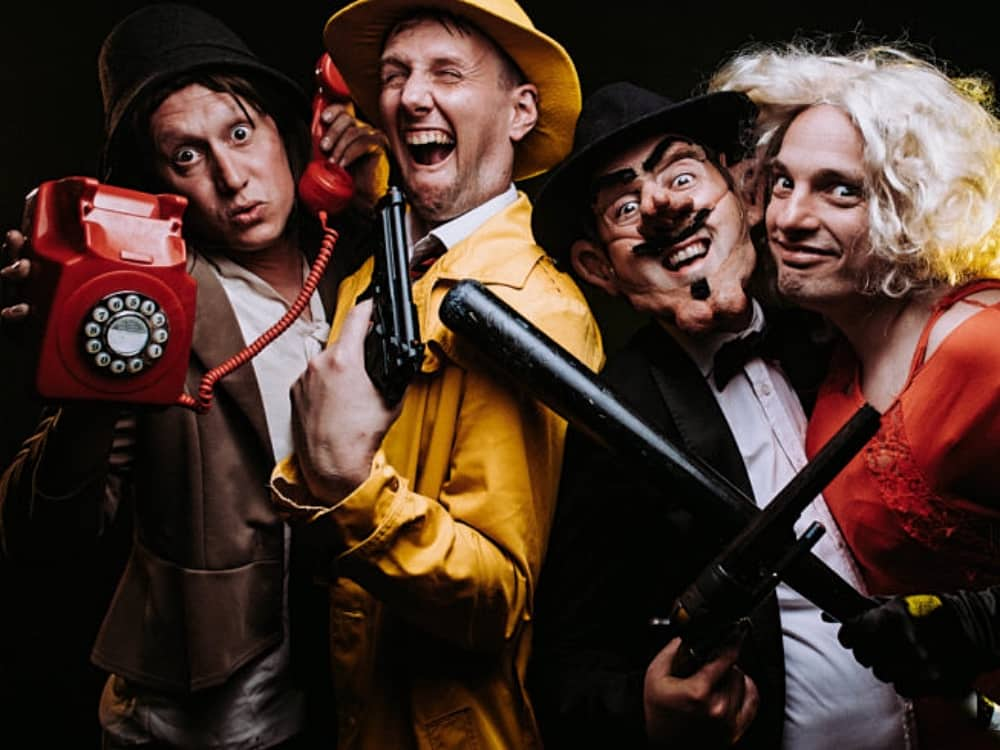 Man hold red retro phone, Dick Tracy comedy wearing mustard coat and har carrying a gun, man in Gaucho disguise and man wearing blonde wig and red dressCorn Ex
