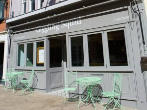 Giggling squid windsor grey frontage and castle green metal table and chairs on pavement