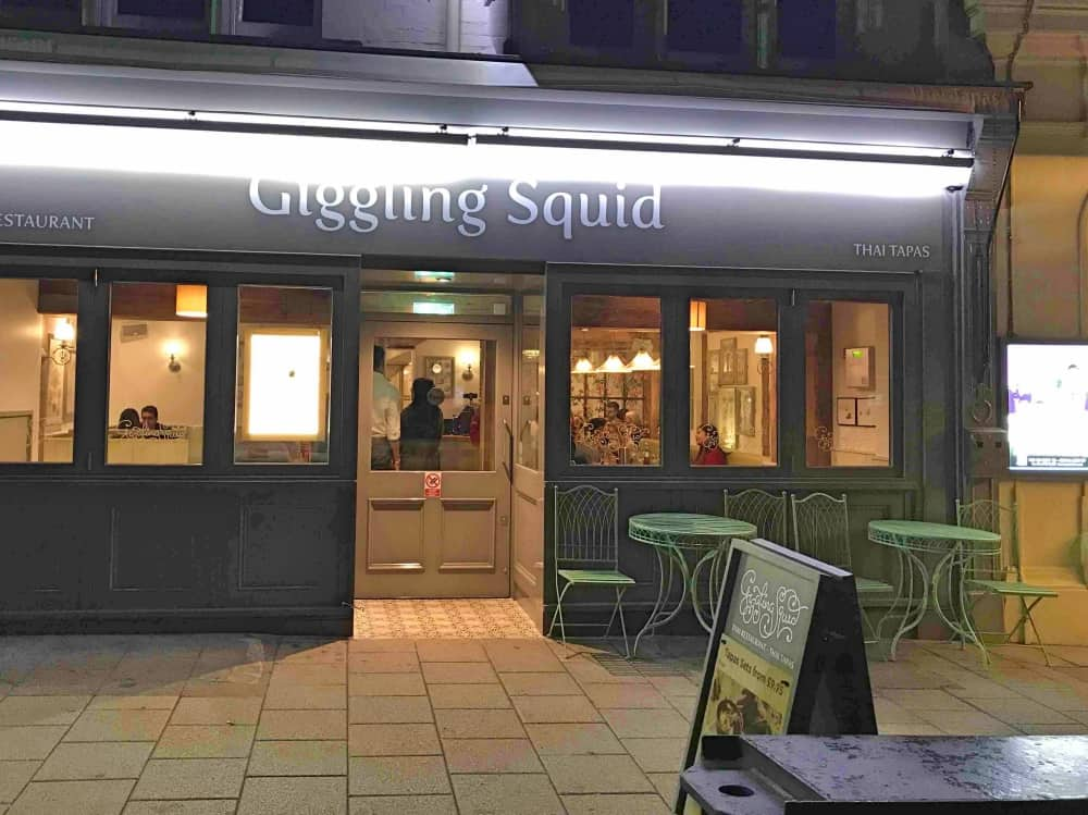 Giggling Squid Windsor Exterior at night grey frontage green metal tables and chairs on pavement