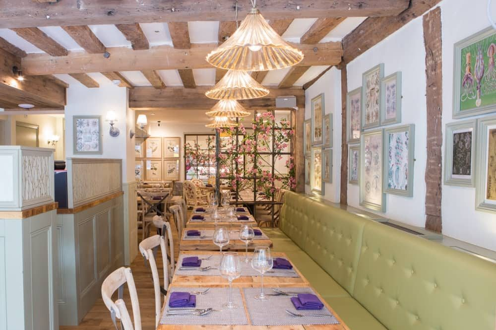 Giggling Squid Windsor exposed wooden beams green banquette pale wood tables and wooden chairs and floor with faux flower wall divider