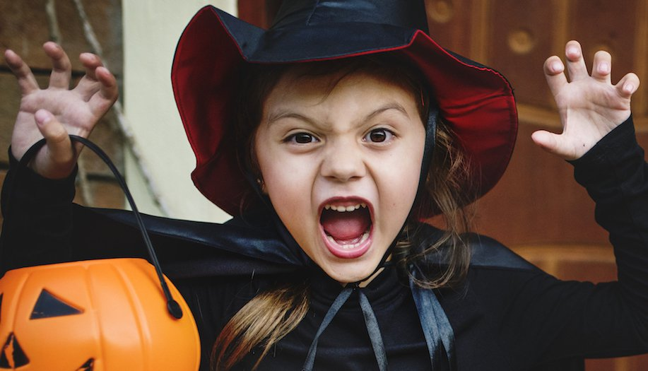 Girl dressed as a witch carrying a pumpkin bucket roaring