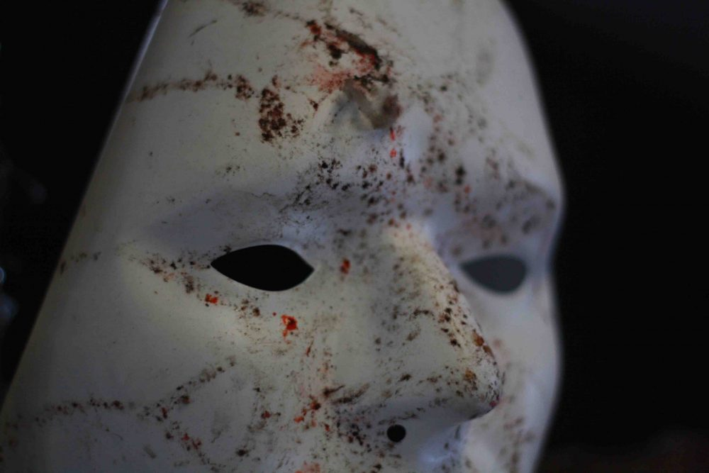 White Halloween mask with mud and bloody marks on it