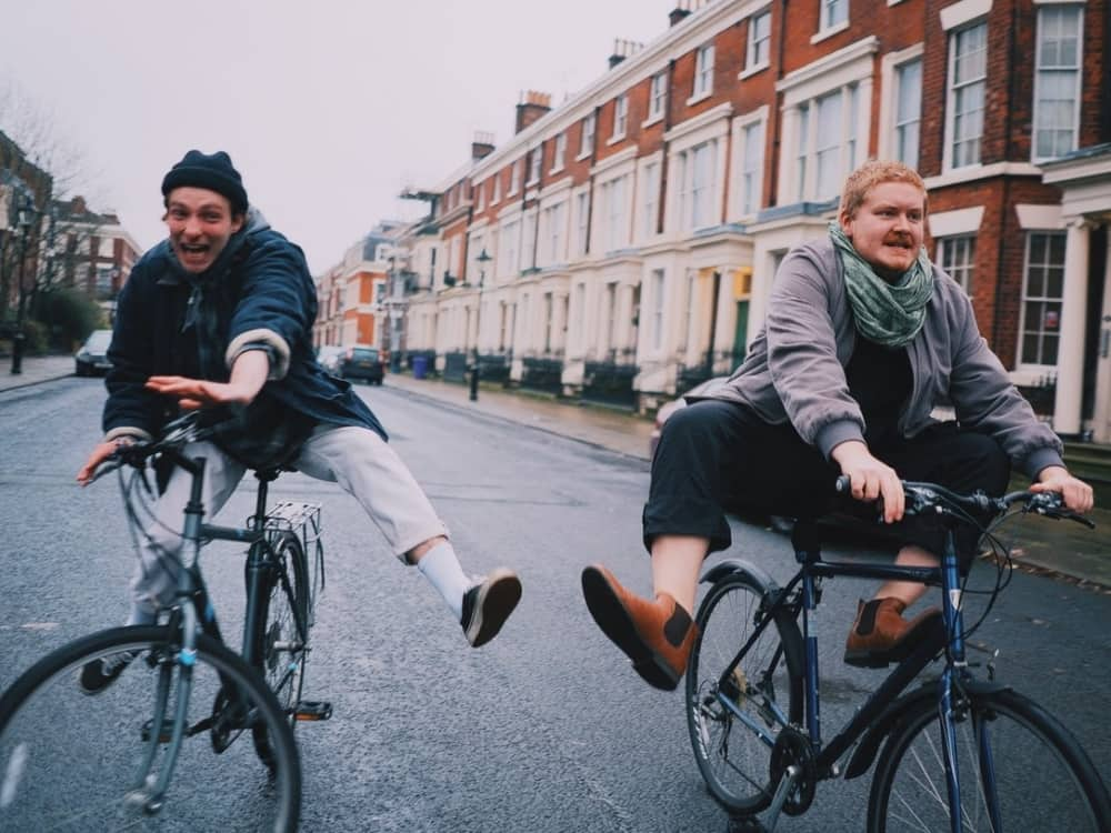 Liverpool pop duo Her's riding bikes down a street terraced houses
