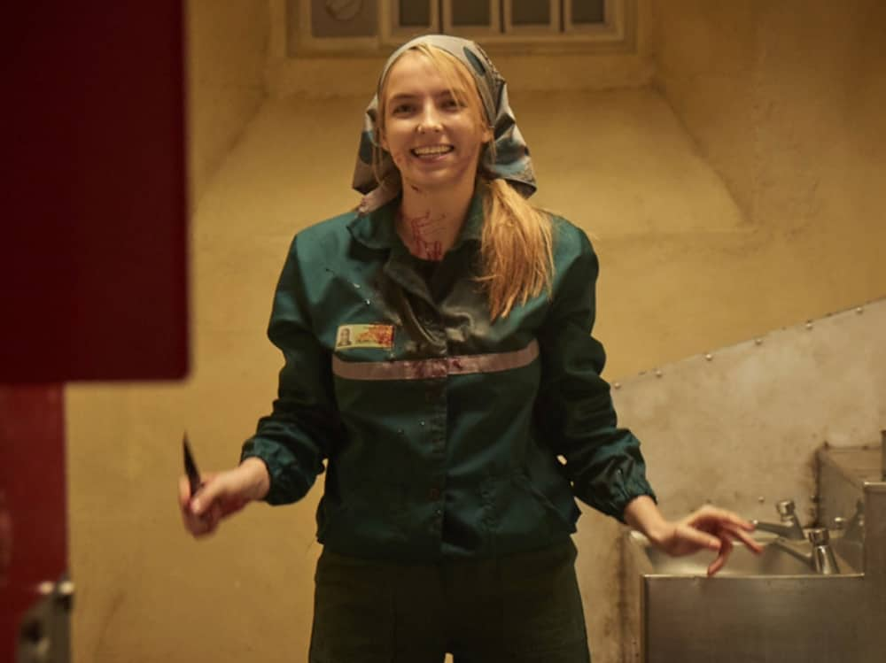 Killing Eve Villanelle in Russian Prisonclothes and head s craft stood with bloody knife in a prison cell