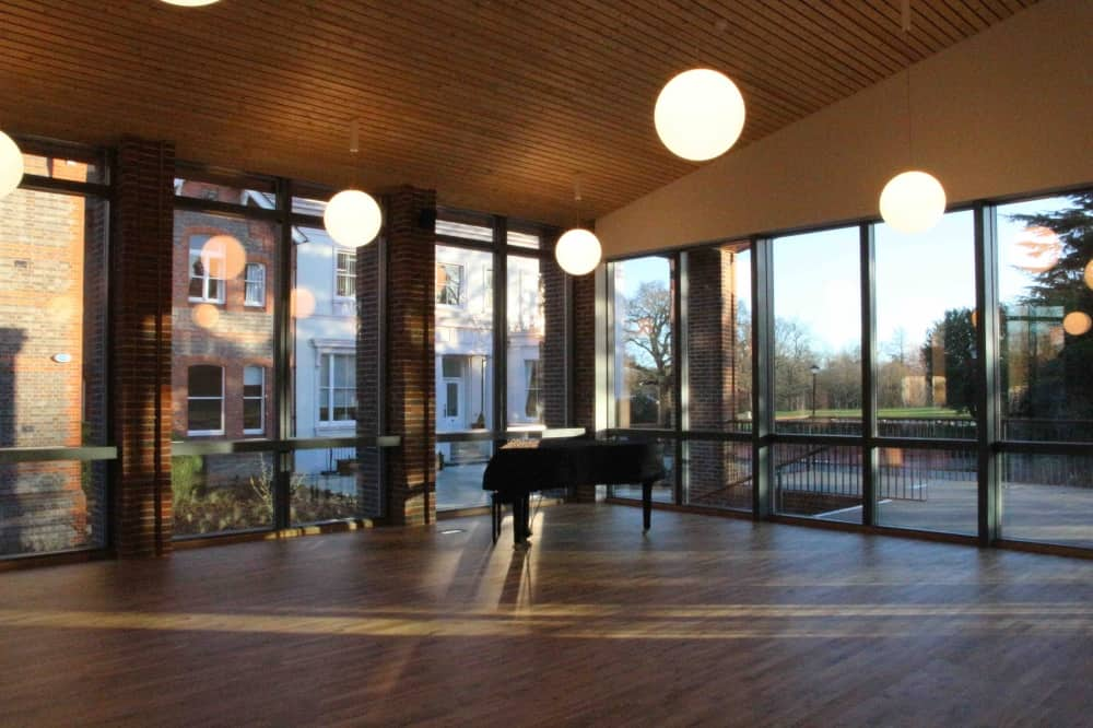 Leighton Park music centre wood and glass with globe lighting piano