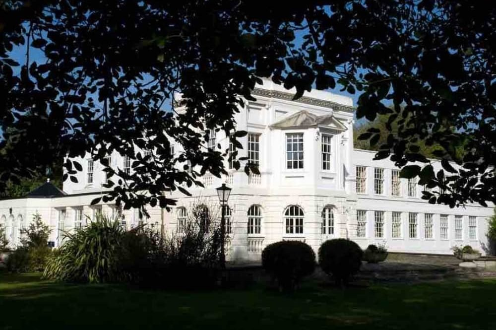 White rendered grade ii listed mansion house on Monkey Island Estate Bray Berkshire shot through the trees