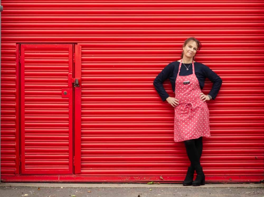 Mrs B's Kitchen Cafein Newbury red corrugated frontage owner Emma wearing black with red spot apron