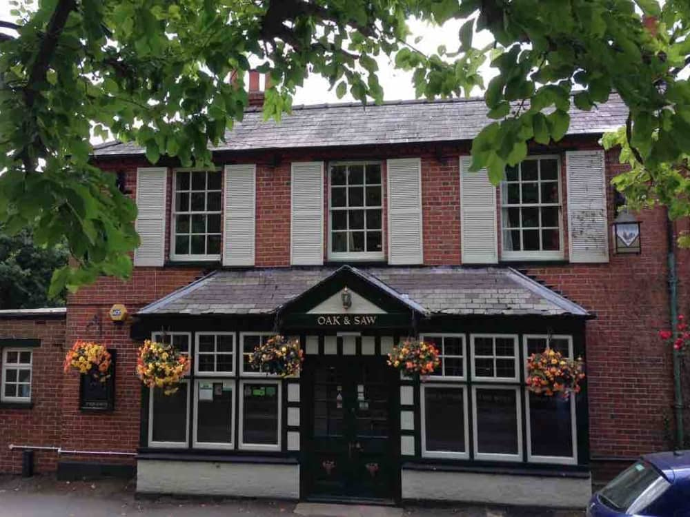The Oak and Saw Pub Taplow red brick building shutters and black and white fascia and window frames hanging baskets