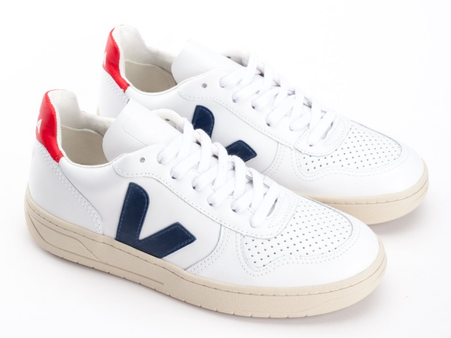 White Veja sustainable trainer with navy blue V and red flash on the back