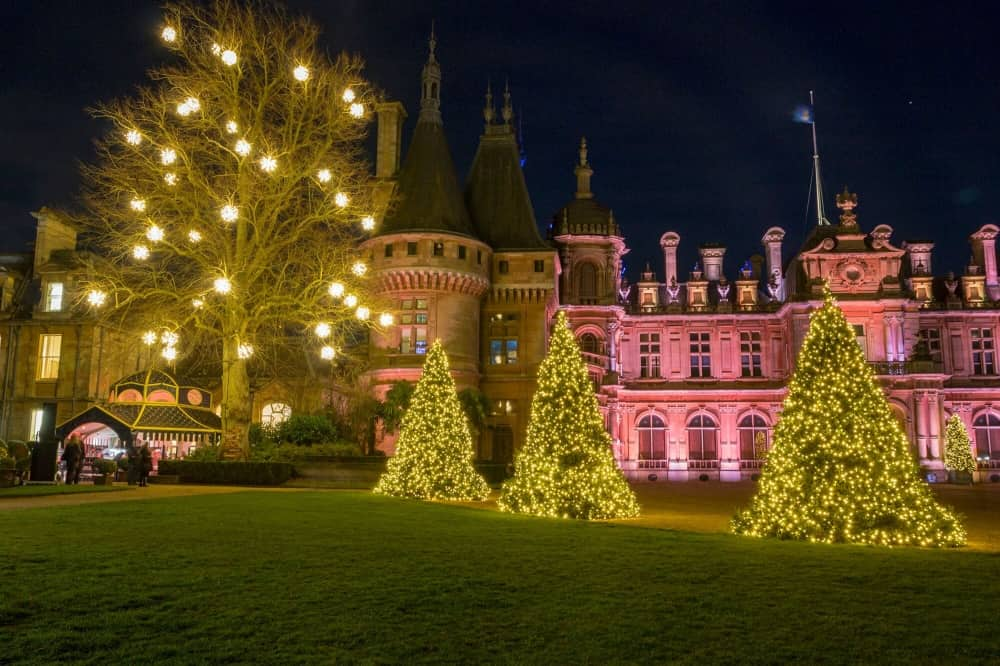 Waddesdon Christmas Market and illuminations colourfully lit period house trees with fairy lights and illuminated christmas trees