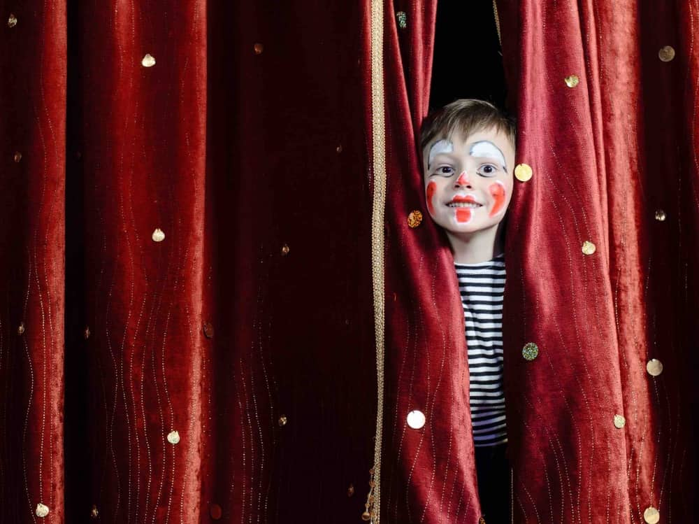 Child on stage peaking through ed velvet curtain painted clown face striped t shirt