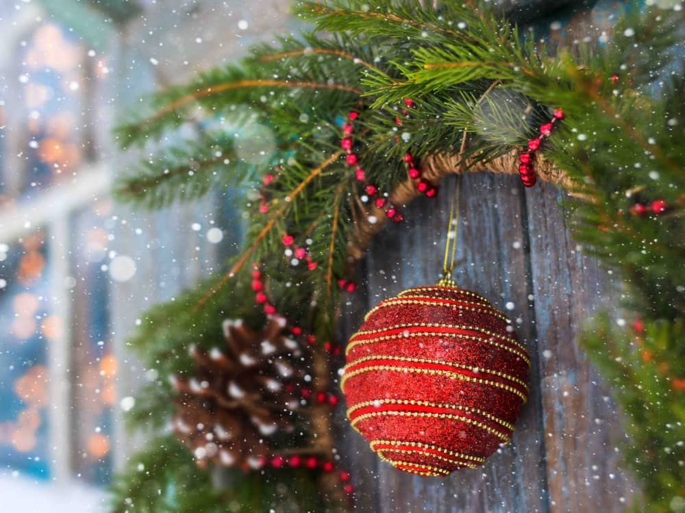 Christmas red bauble and pine cone hanging from fir wreath on door of chalet in snow