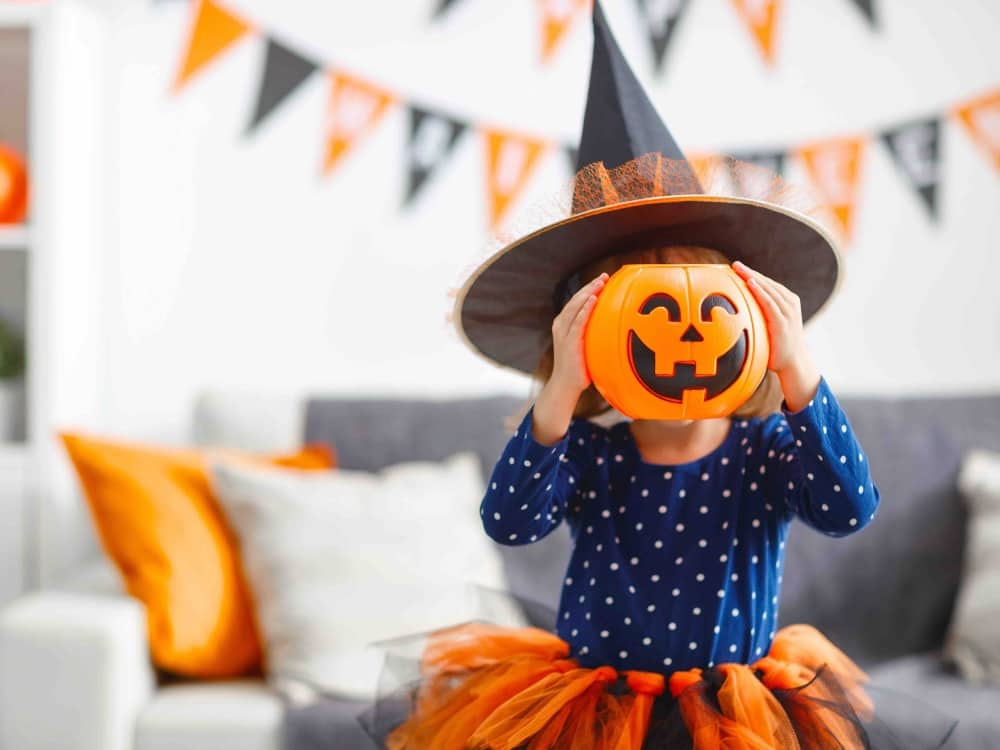 Little girl win blue star top orange tutu witches hat and pumpkin face
