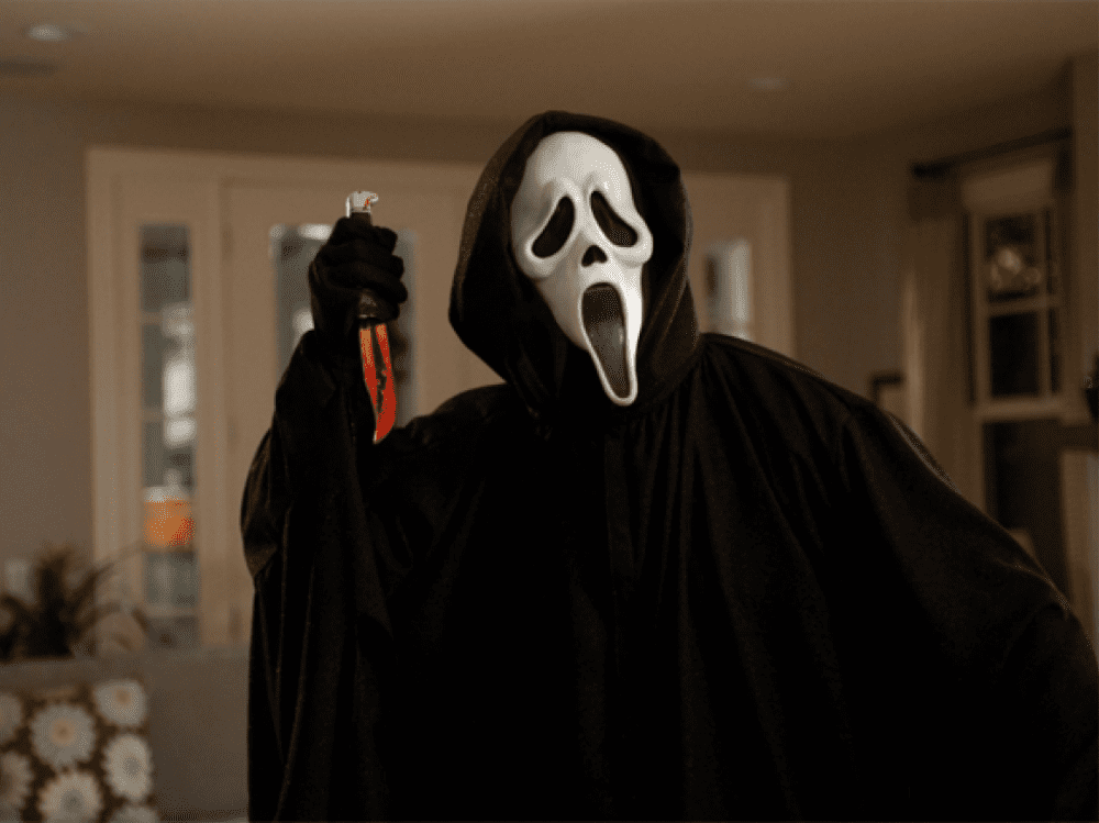 Cream film black cloaked person wielding knife and scary white mask