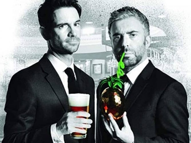 Black and white image of two men in black suits and ties one holding a pint the other a cocktail