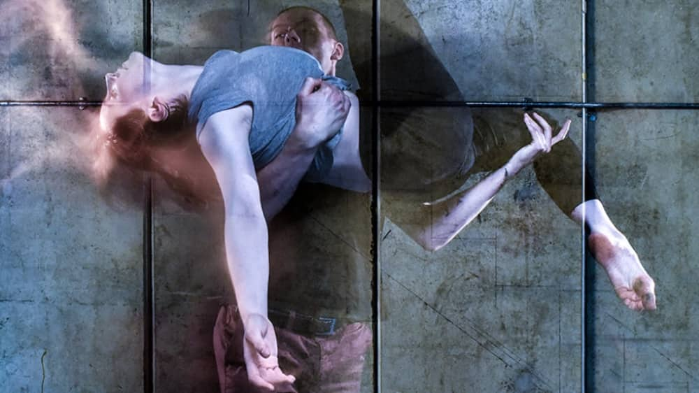 Blurry image of two dance in a lift against a mental background – company Chameleon 10