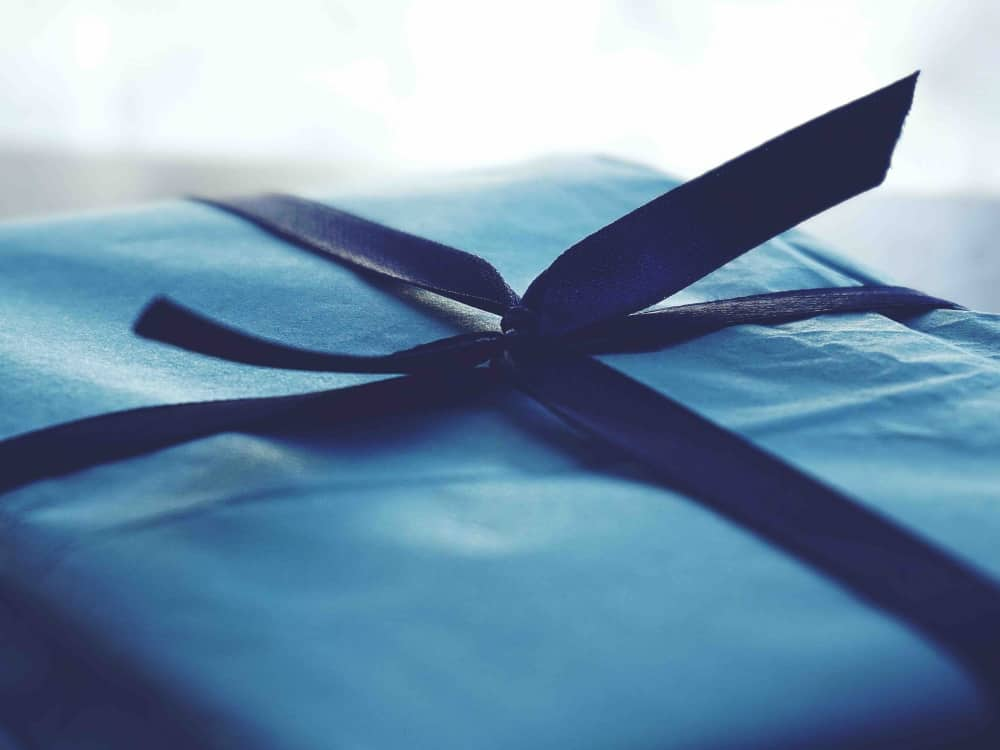 Blue tissue wrapped gift with blue ribbon