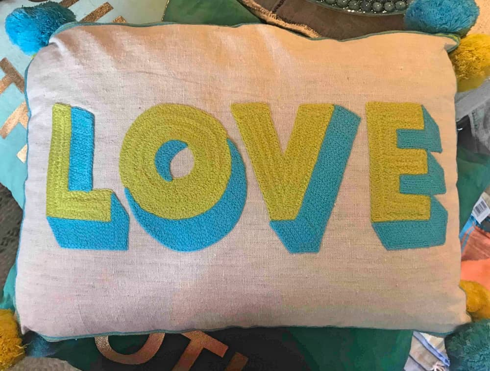 Neon green and turquoise blue Love cushion with pom poms
