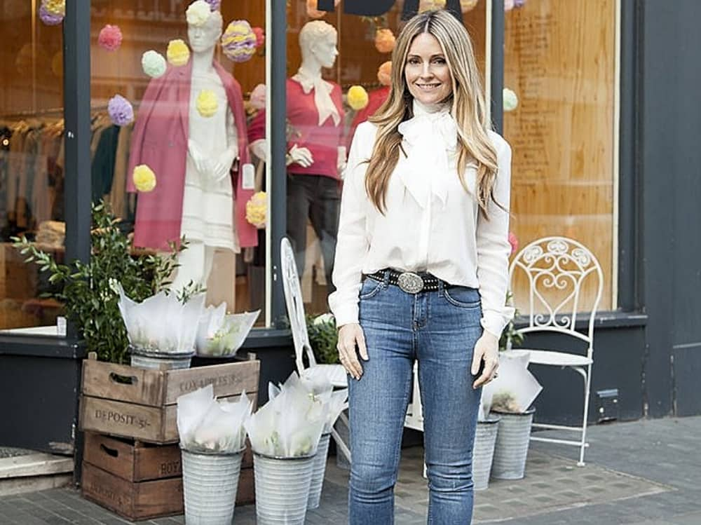 Denim designer Donna Ida white blouse blue jeans in front of shop