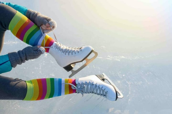 Woman wearing multi coloured stripy socks lacing up ice skates