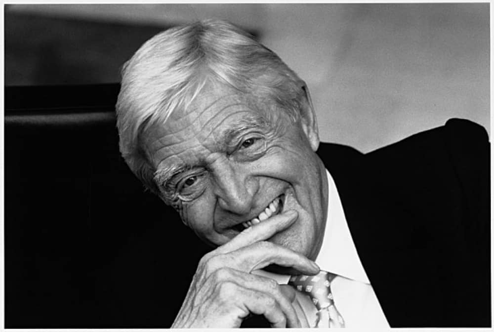 black and white image of legendary broadcaster Sir Michael Parkinson suit and tie laughing with hand to mouth