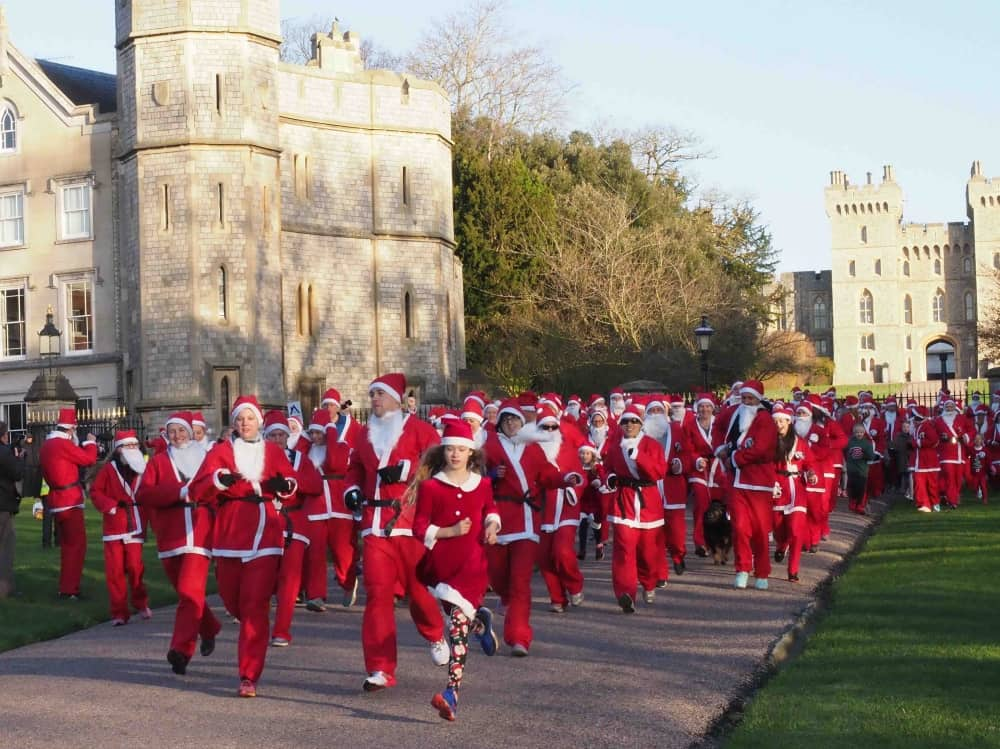 Santa Dash Windsor runners dressed as Father Christmas running Long Walk Windsor with Windsor Castle in the background
