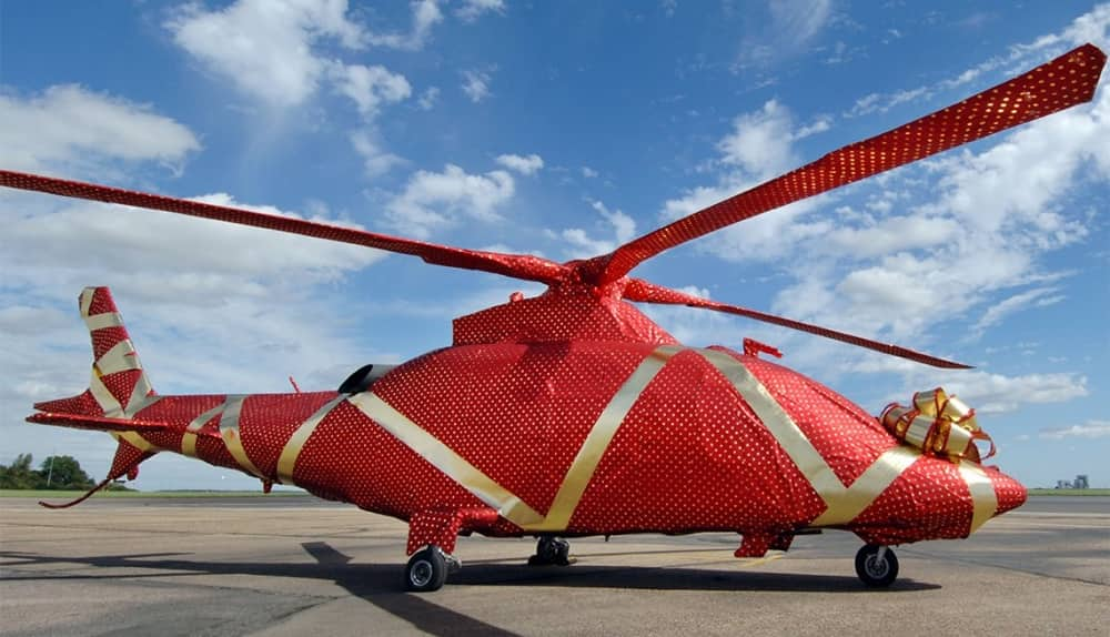 helicopter wrapped in red wrapping paper and gold ribbon