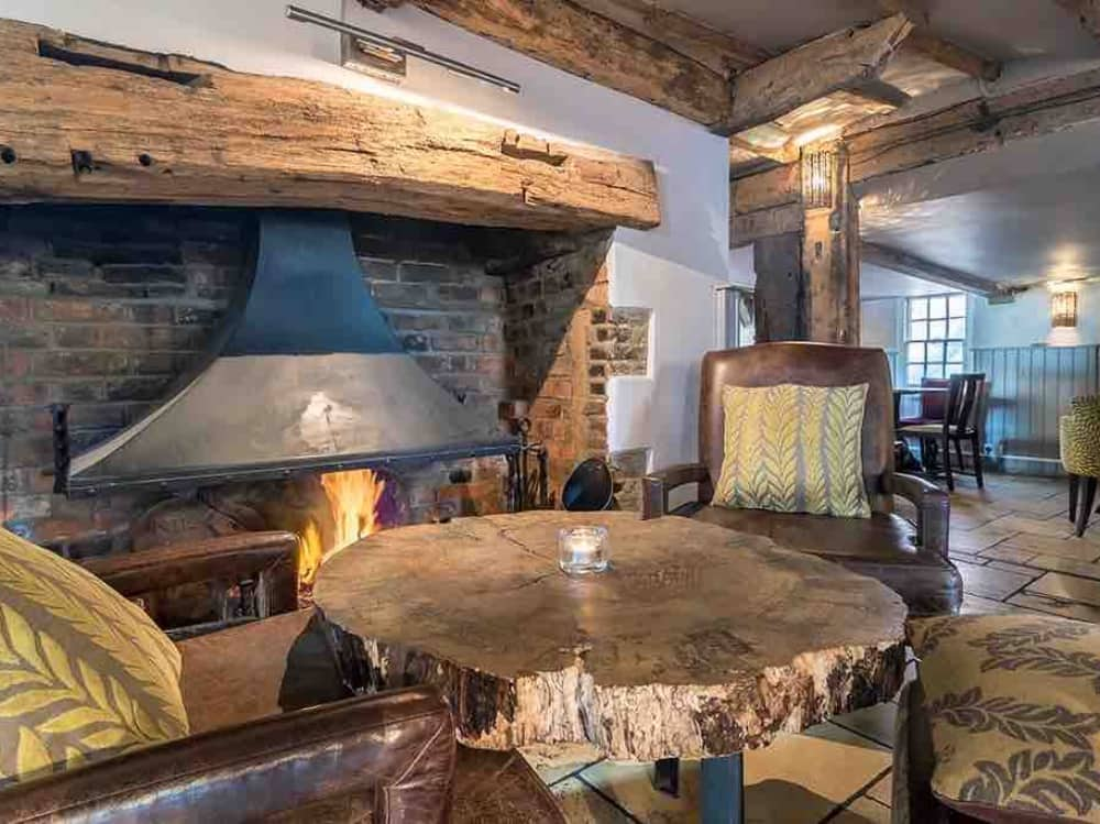 open fire with steel chimney comfy chairs mustard cushions stone floorr grey walls