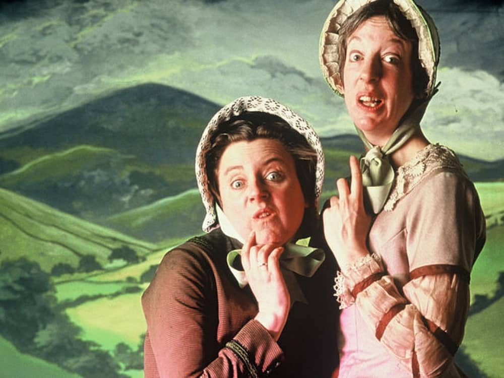 Background image of rolling hills and two men dressed as women Withering Heights