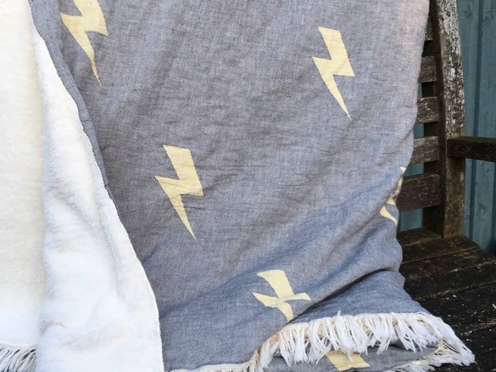 Cotton and fleece throw with lightening bolt appliqué draped over bench The Corner Shop Woolhampton
