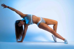 Women in grey calvin klein sports bra and pants balancing on one hand stretching