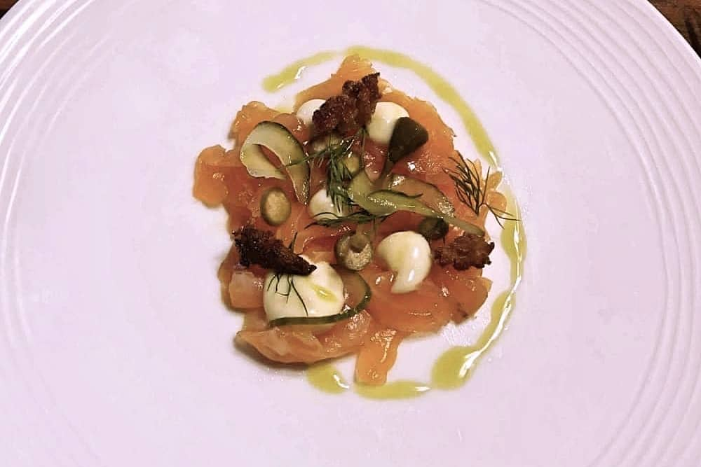 Salmon starter on a white plate The crown at Bray heston Blumenthal