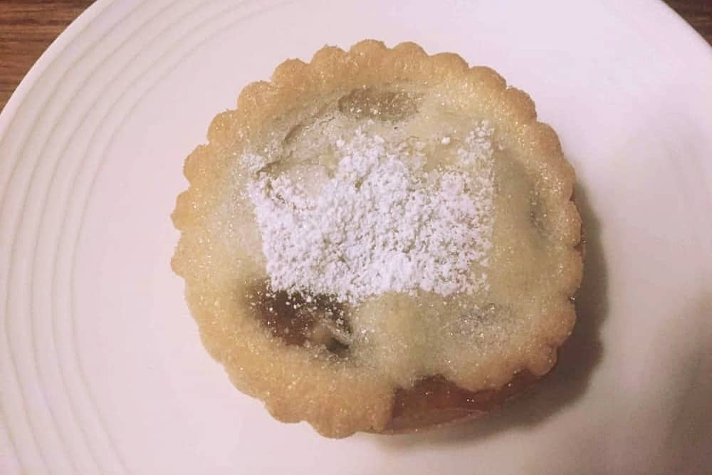 Mince pie with crown dusted in sugar on white plate Crown at Bray Heston Blumenthal