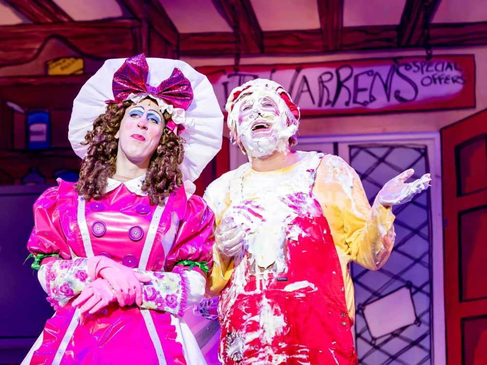 Steven Blakeley panto dame pink dress and white hat with pink ow and Kevin Cruise Idle Jack Dick Whittington red dungarees and yellow t shirt foam on face