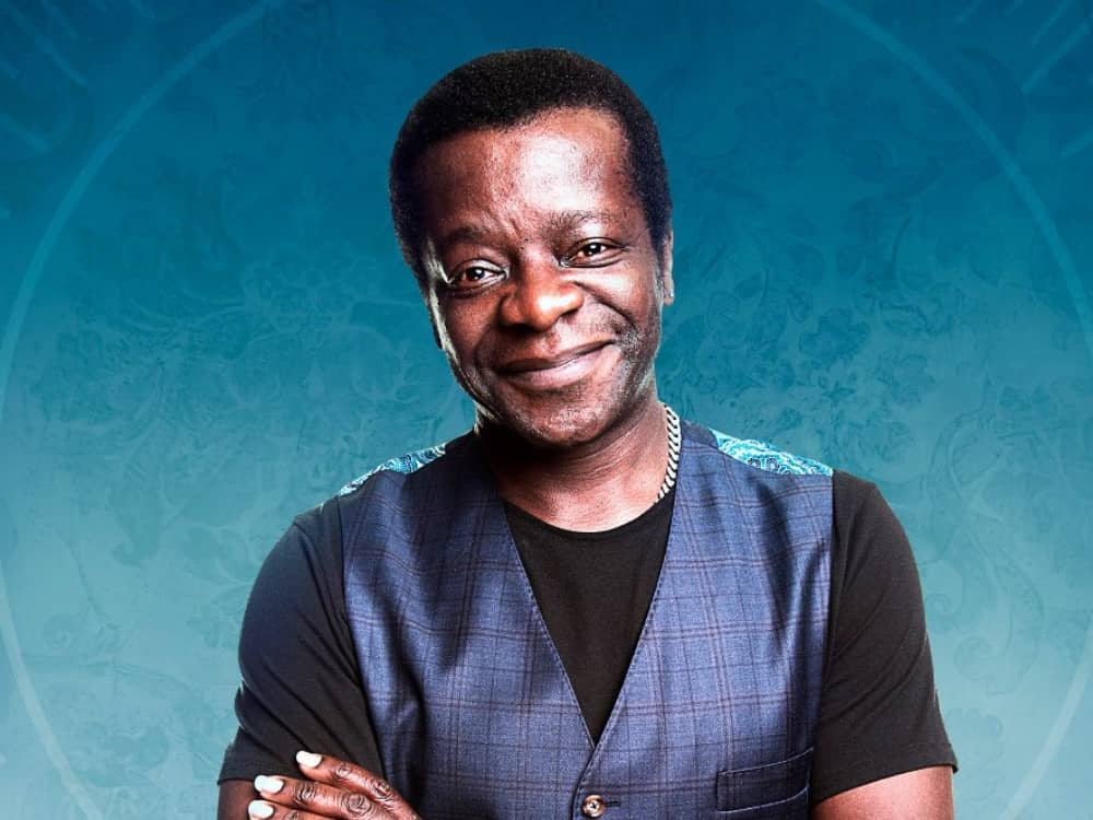 Comedian Stephen K Amos black t shirt waistcoat blue background