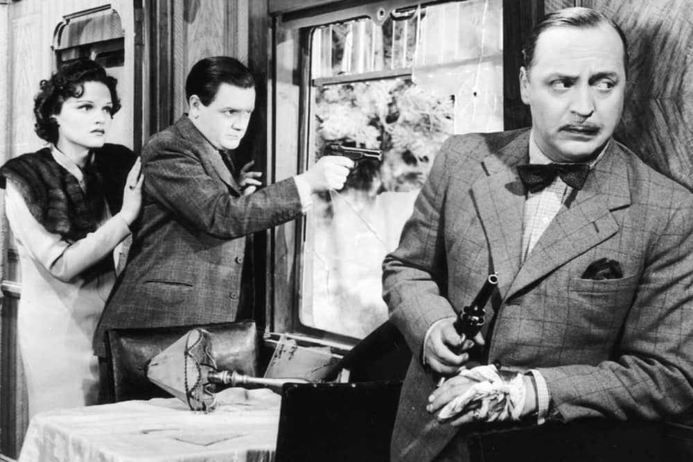 Alfred Hitchcock The Lady Vanishes suited gunmen and woman in tweed suit and fur collar