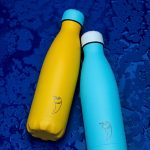 Chilly yellow and blue metal bottles on royal blue background