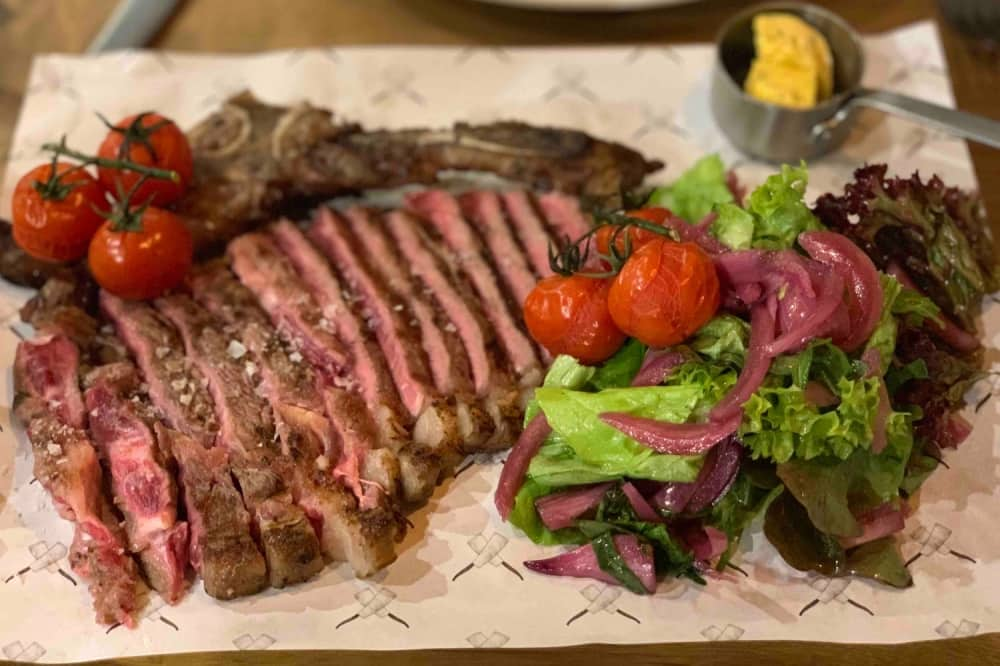 Sliced sirloin steak with salad and roasted tomatoes on vine Corn Stores Reading