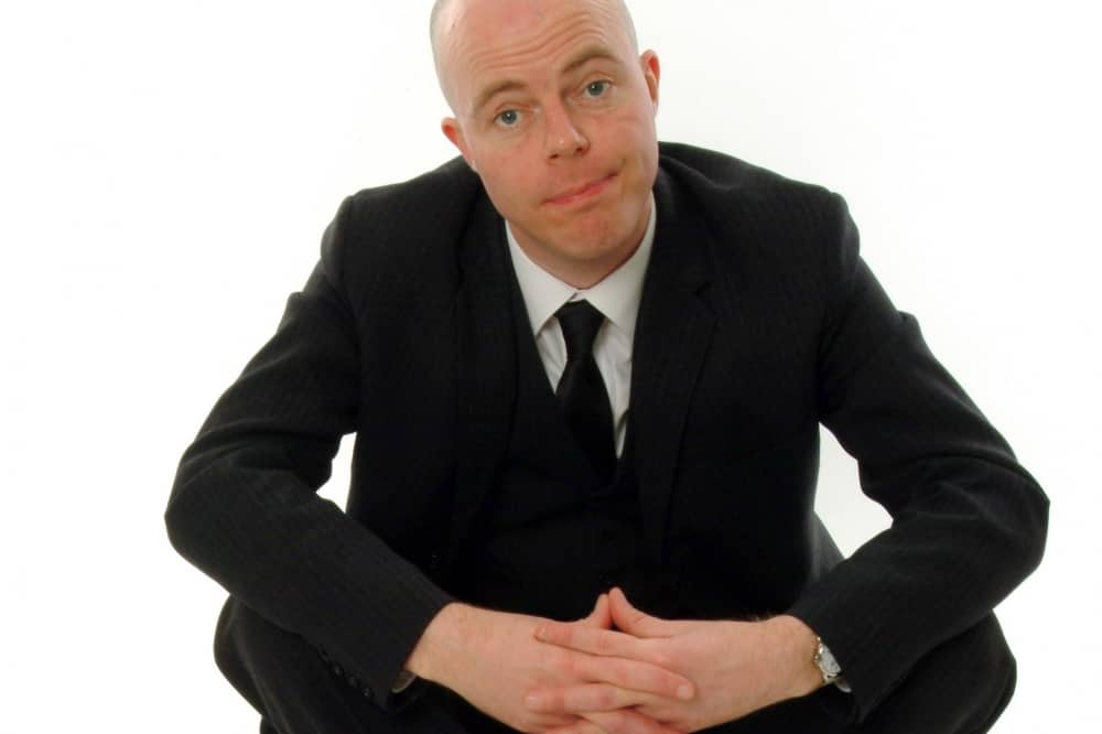 Comedian Roger Monkhouse Black suit bald head hands clasped