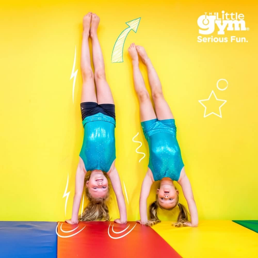 Two girls hand stand against yellow wall