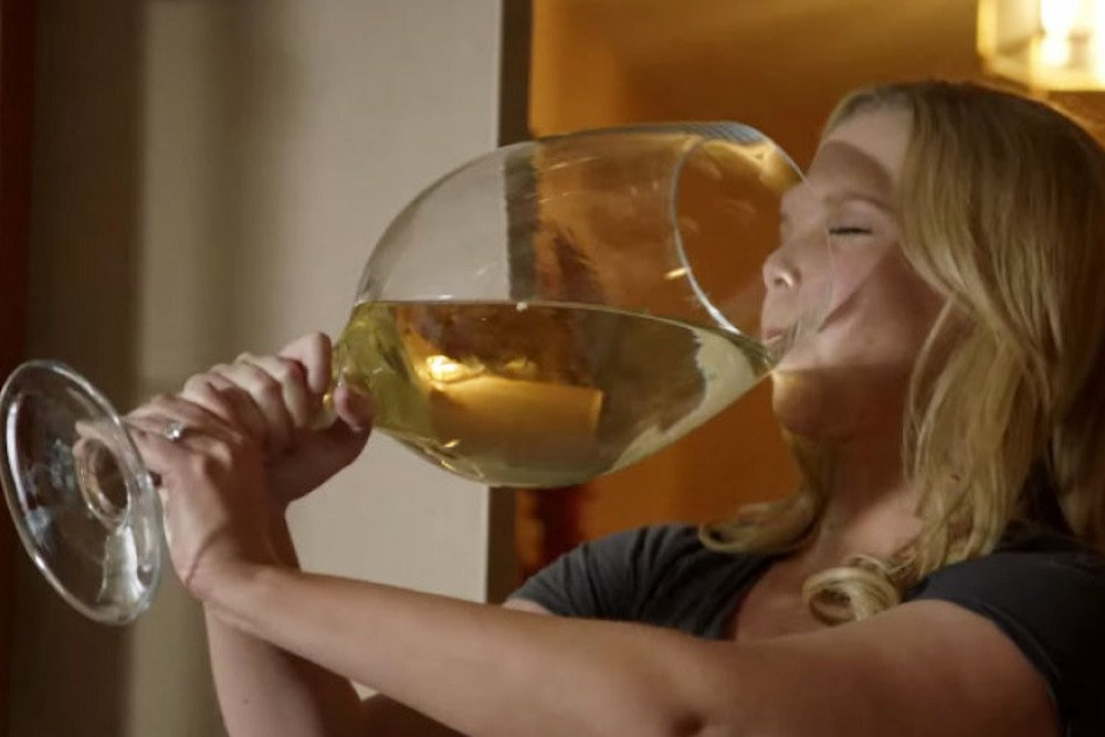 Actress Amy Schumer drinking a comedy sized giant glass of white wine