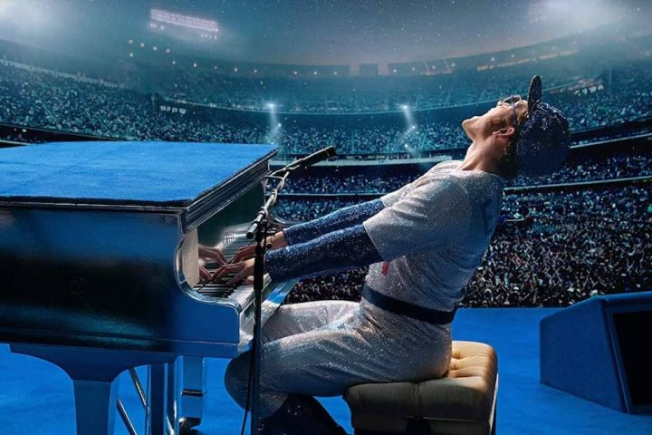 Singer Elton John baseball outfit and cap playing piano at gig
