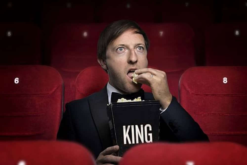 Comedian Andrew Maxwell red cinema seat eating popcorn