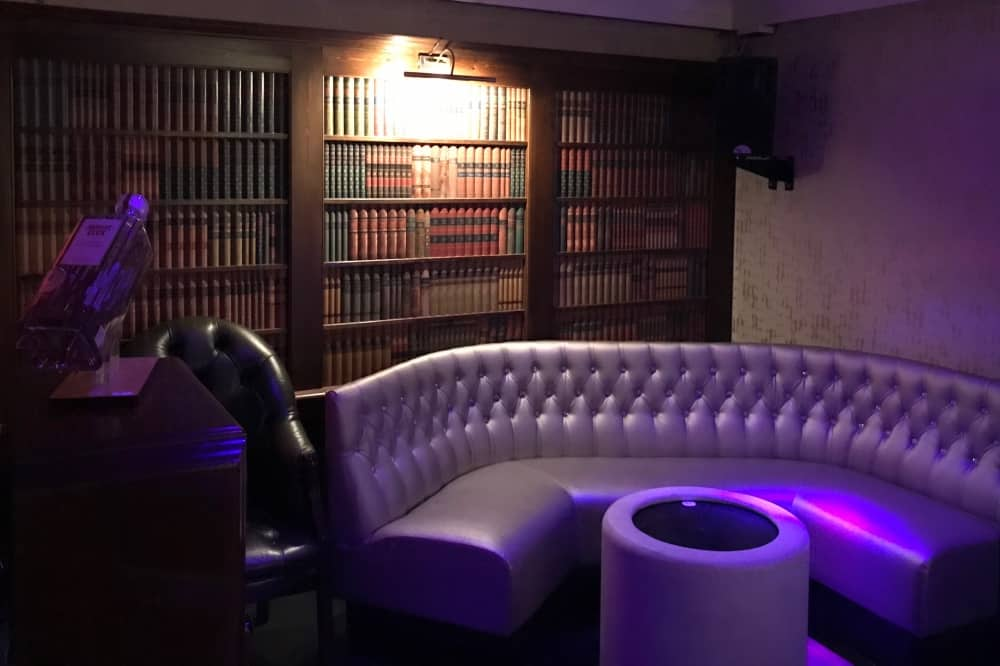 Ascot Fifty 5 VIP area silver leather banquette with library wallpaper and low tables