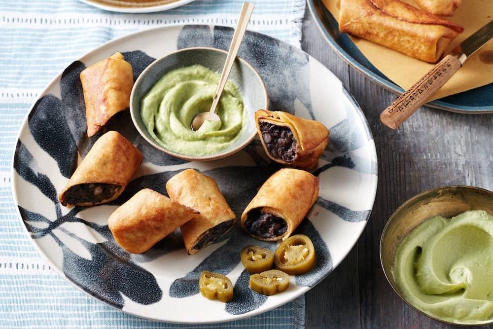 chimichangas on botanic plates with avocado dipping sauce