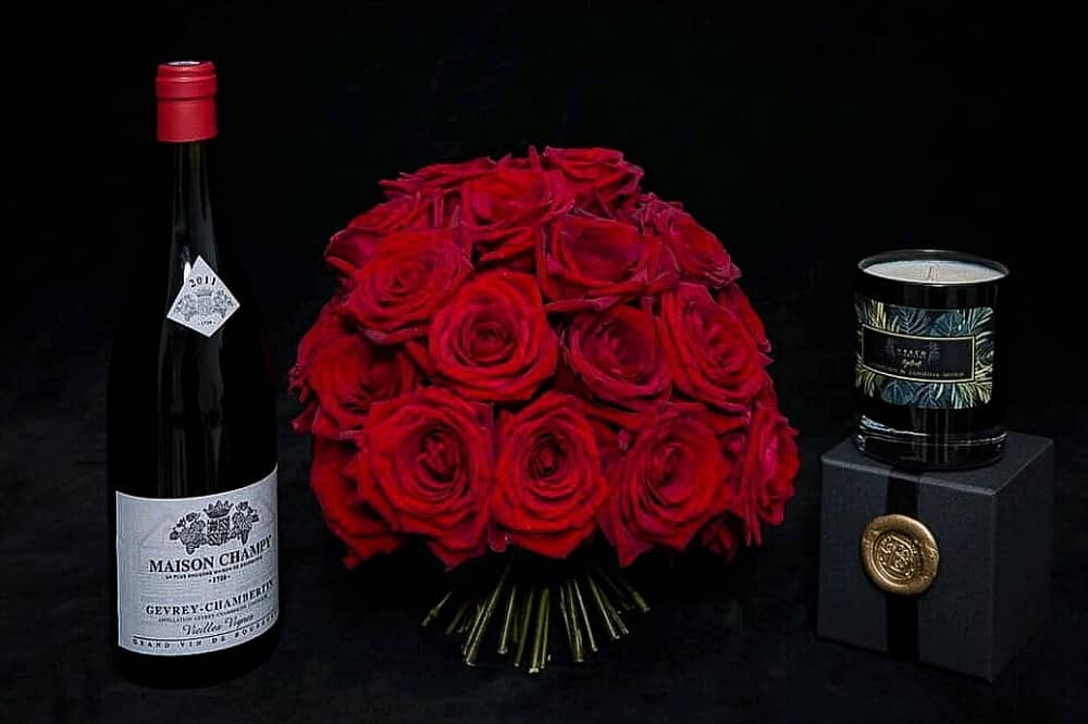 Bottle of wine red roses and candle draco floristry