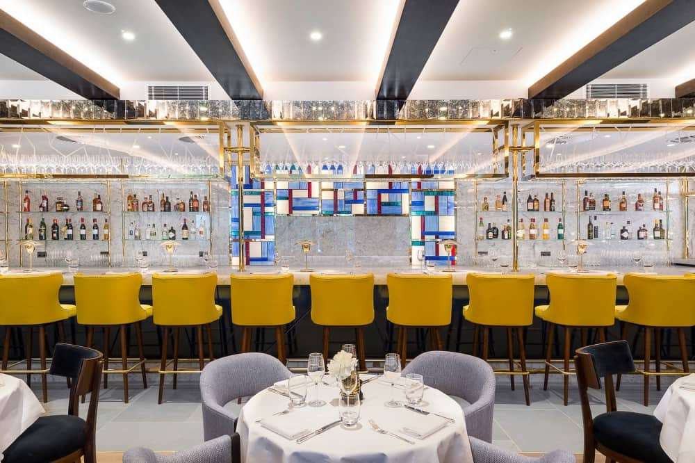 Yellow velvet bar stool stained glass bar and seating Devonshire Club bar brasserie LONDON